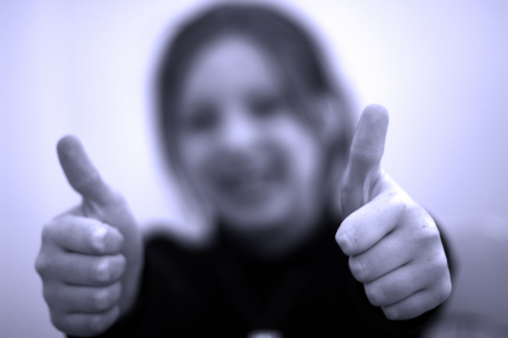 An image showing a child in a thumbs up pose