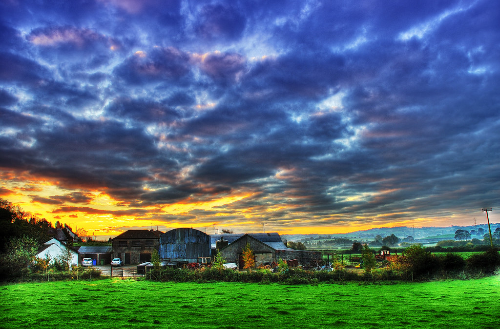 Image depicting a farm with a dramatic sky