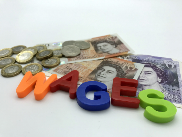 Image showing the word 'wages' spelled out with some cash behind.