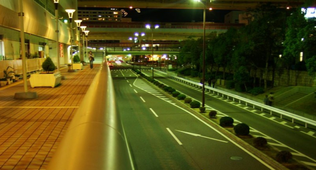 An image showing an urban road at night with very little traffic