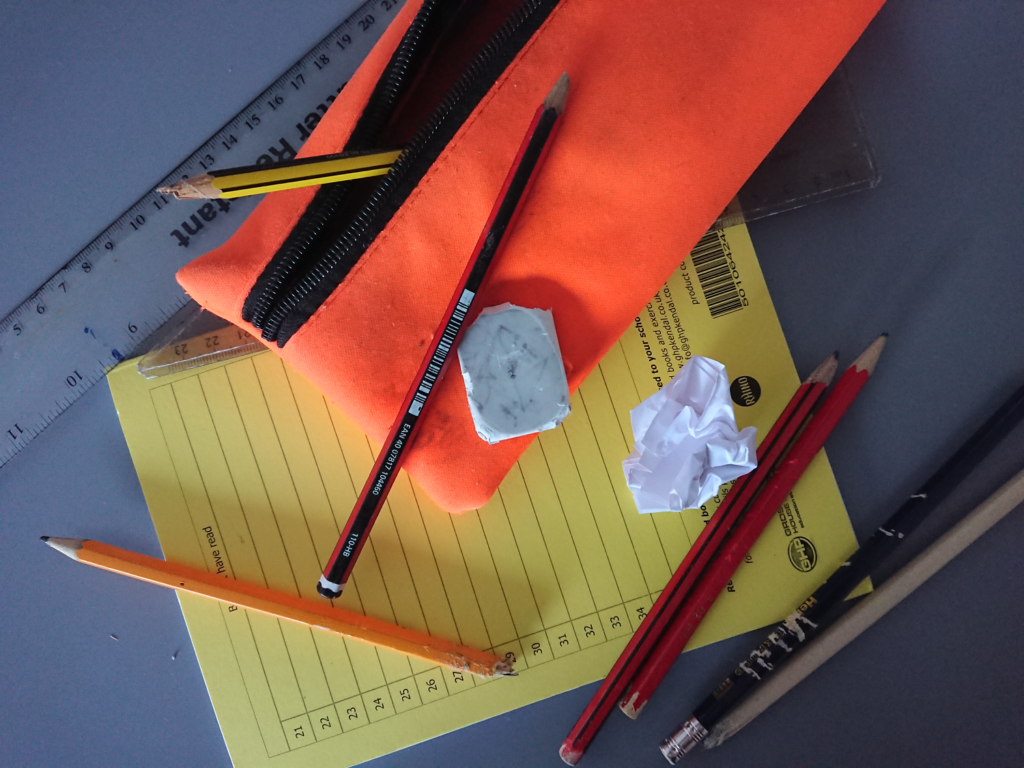 A picture showing some scruffy stationery items on a school desk