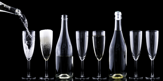 A black and white image showing a row of glasses and a bottle